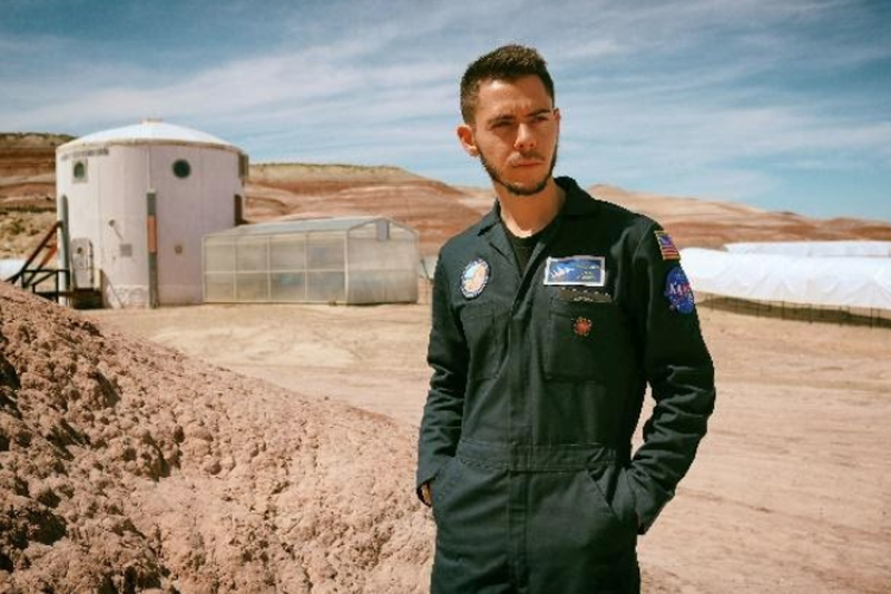 Commander Dylan Dickstein in front of the habitat (left) and greenhouse (center)