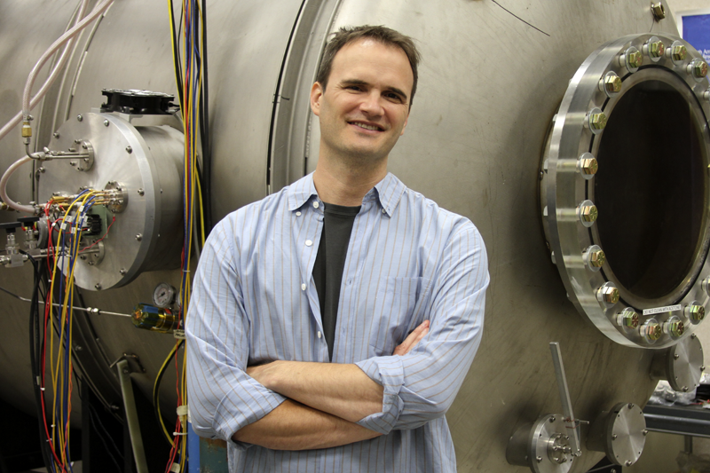 Richard Wirz standing in front of a large vacuum chamber used to test high-power electric propulsion systems